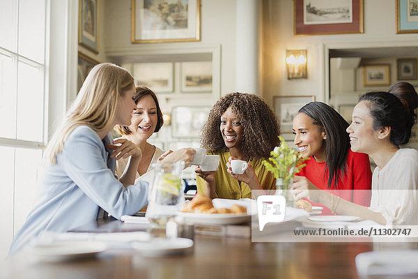 Lächelnde Frauen beim Kaffeetrinken und am Restauranttisch