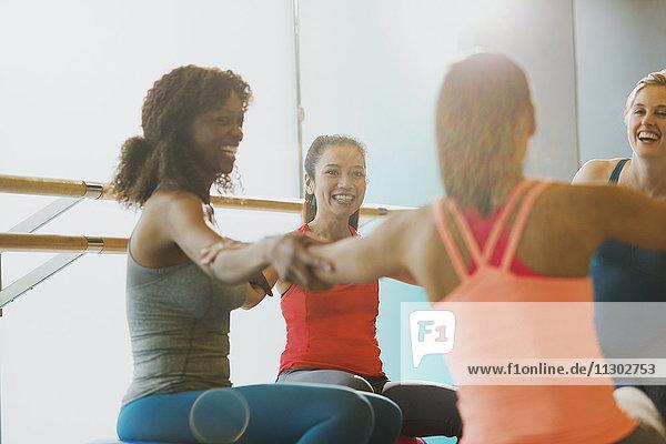 Lächelnde Frauen im Kreis im sonnigen Fitnessstudio
