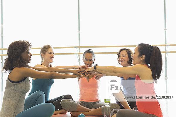 Lächelnde Frauen  die im Fitnessstudio die Hände berühren
