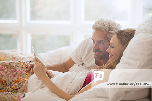 Couple relaxing laying in bed using digital tablet