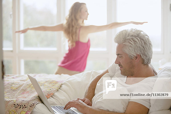 Woman practicing yoga warrior 2 pose in bedroom with husband using laptop in bed