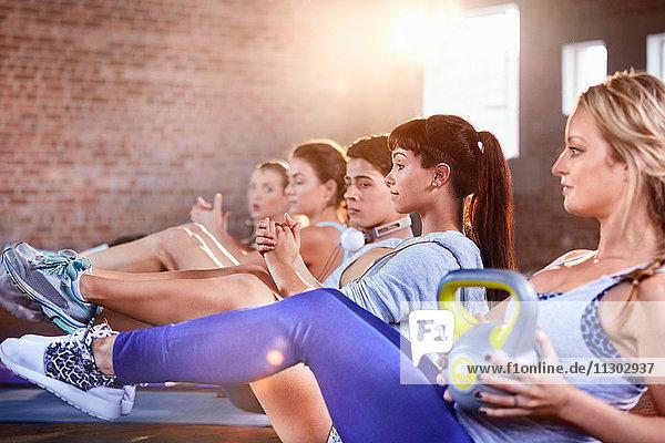 Junge Männer und Frauen mit Kettlebells im Fitnessstudio der Übungsklasse