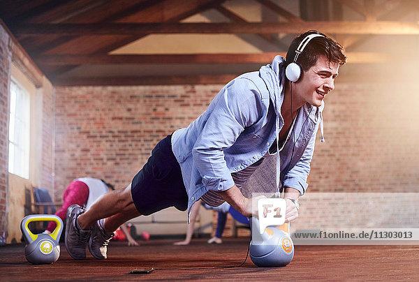 Entschlossener junger Mann mit Kopfhörer  der Liegestütze mit Kettlebell macht.
