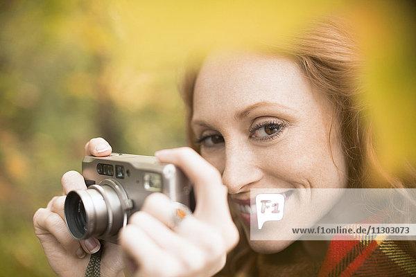 Close up smiling woman using digital camera among autumn leaves