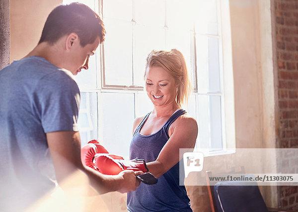 Trainerin hilft jungen Boxerinnen beim Anziehen von Boxhandschuhen im Studio