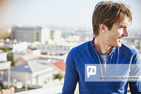 Smiling male runner looking away in sunny city