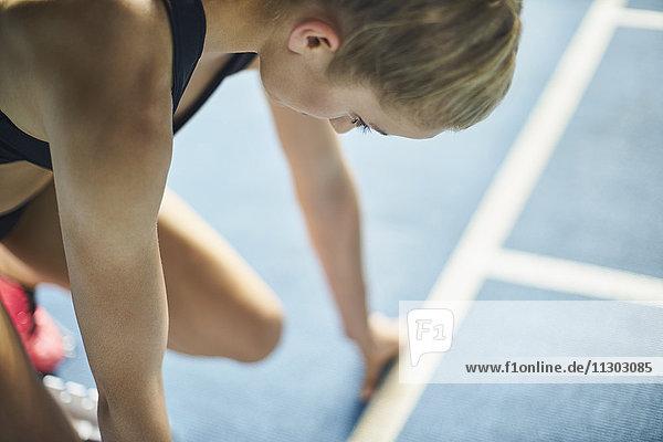 Fokussierte Läuferin bereit zum Start auf der Sportbahn