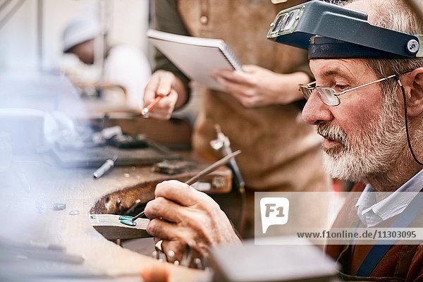 Focused jeweler working in workshop