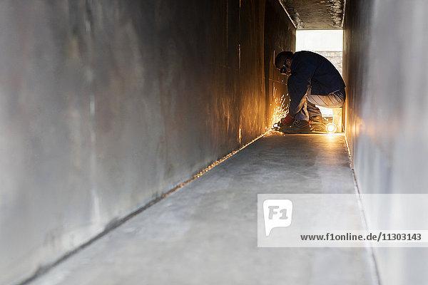 Schweißer mit Schweißbrenner im Stahltunnel