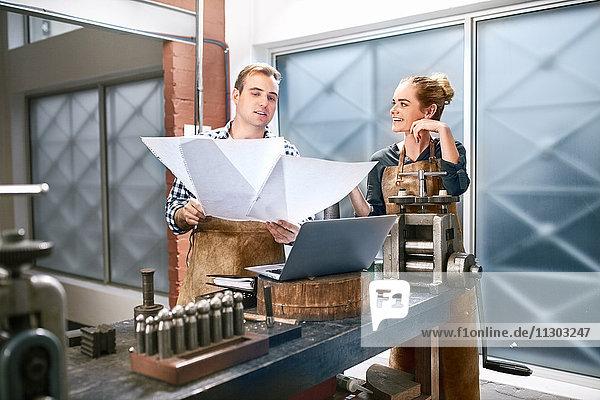 Juweliere beim Betrachten von Blaupausen am Laptop in der Werkstatt