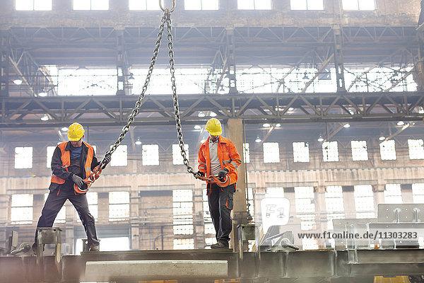 Stahlarbeiter mit Kranhaken im Werk