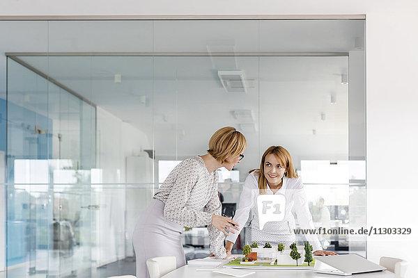 Architektinnen diskutieren Modell im Konferenzraum