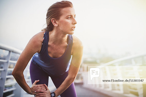 Female runner stretching leg on urban footbridge