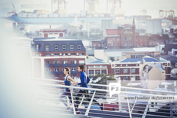 Runner couple running on urban footbridge