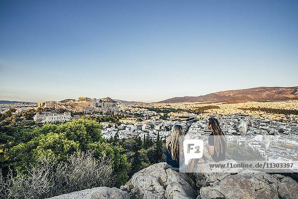 Paar auf Felsen mit Blick auf die Landschaft  Athen  Griechenland