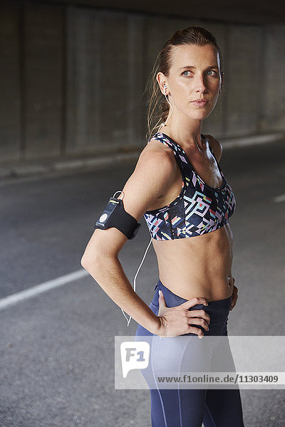 Serious fit female runner in sports bra with mp3 player armband and headphones on urban street