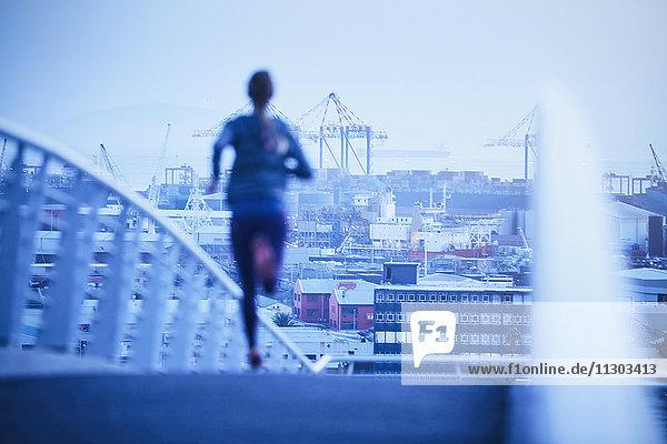 Female runner running on urban footbridge at dawn