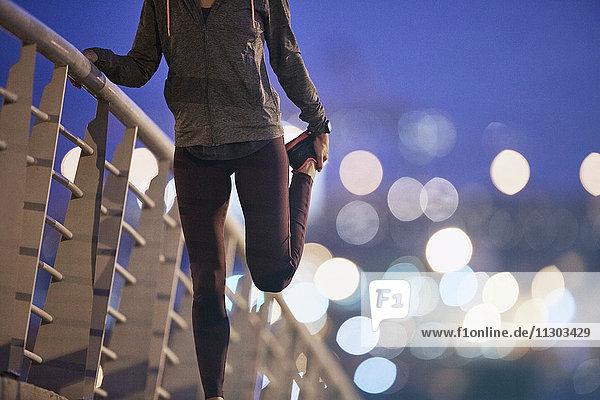 Female runner stretching leg on footbridge at dusk