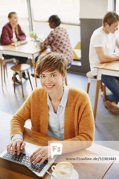 Portrait smiling businesswoman drinking coffee working at laptop in cafe