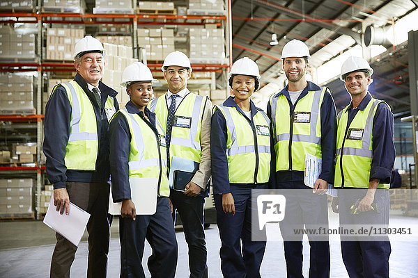 Portrait confident managers and workers in distribution warehouse