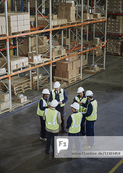 Manager and workers meeting in circle in distribution warehouse