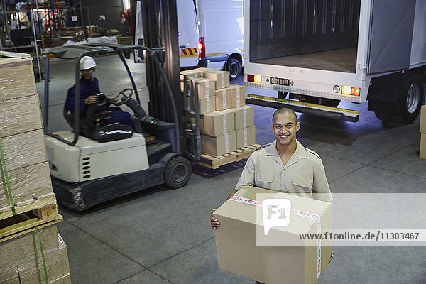 Portrait smiling worker carrying cardboard box at distribution warehouse loading dock