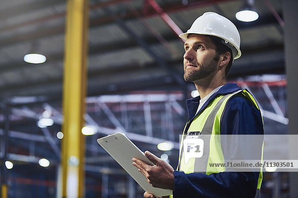 Worker with clipboard looking up in distribution warehouse