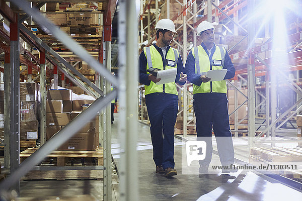 Workers walking with clipboards in distribution warehouse