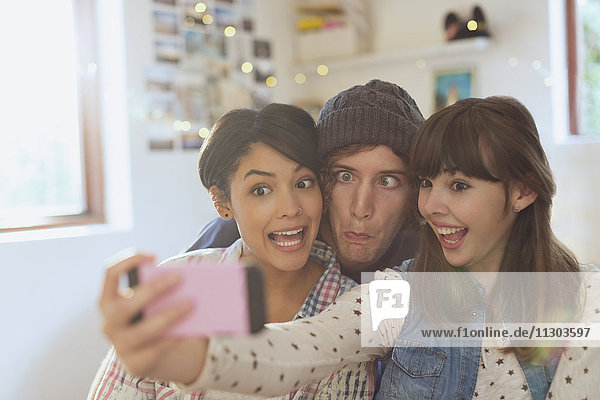 Playful young friends taking selfie making silly faces