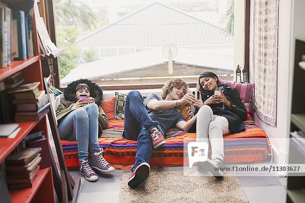 Young friends hanging out using cell phones in apartment window
