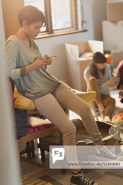 Young woman texting with cell phone in new apartment