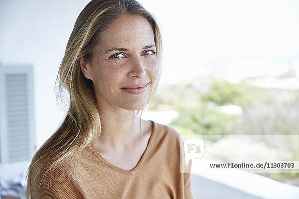 Portrait smiling blonde woman on patio