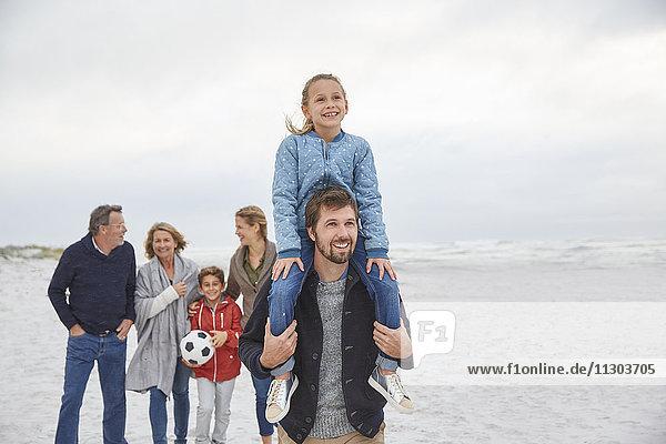 Multi-generation family walking on winter beach