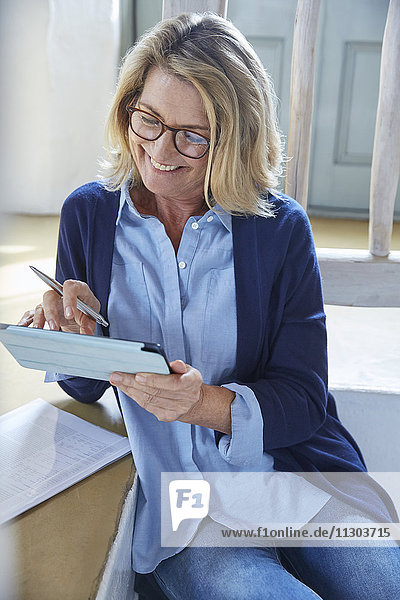 Smiling senior woman using digital tablet