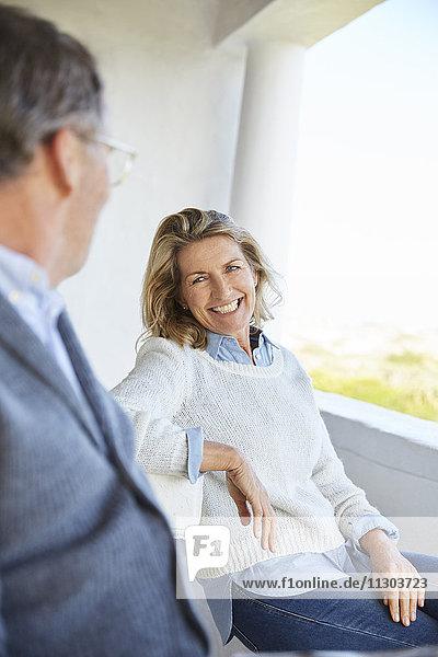 Smiling senior couple talking on patio