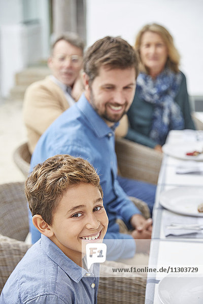 Portrait smiling boy enjoying lunch with family on patio