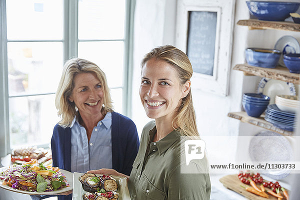 Portrait smiling mother and daughter serving food