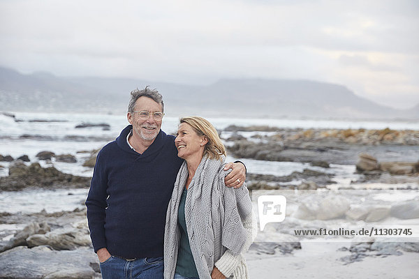 Smiling senior couple walking on winter beach