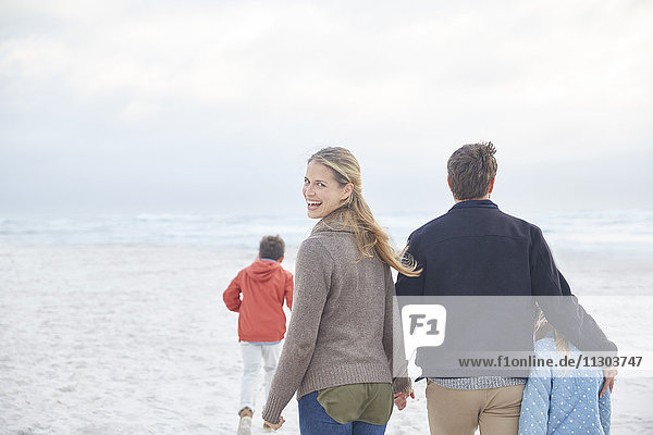 Portrait happy family walking on winter beach