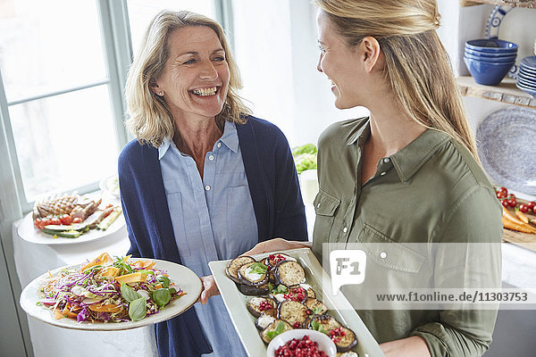 Smiling mother and daughter serving food