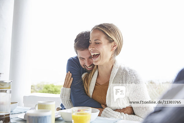 Affectionate couple hugging and laughing at breakfast on patio