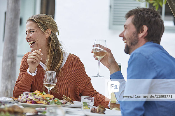 Laughing couple drinking white wine and eating lunch at patio table