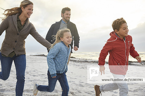 Playful family running on winter beach