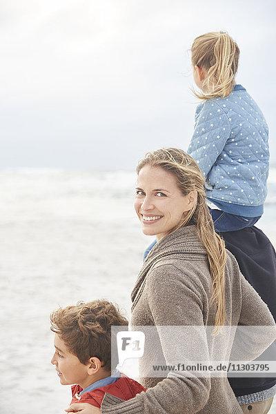 Portrait smiling family walking on winter beach