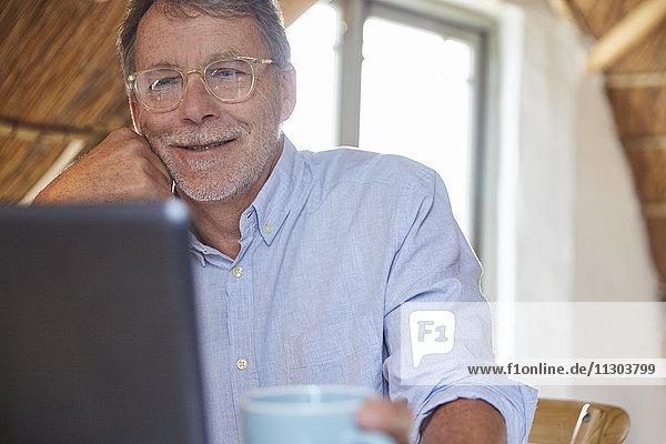 Senior man drinking coffee and using laptop
