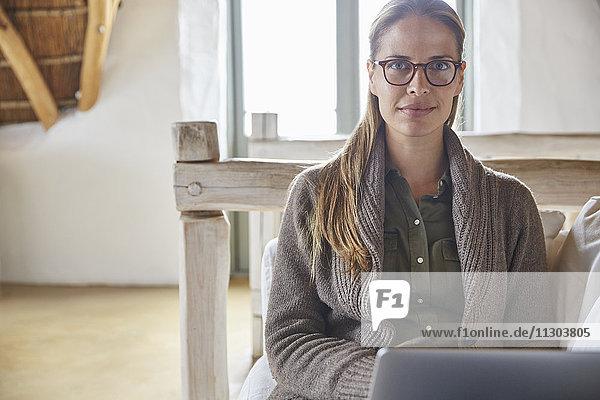 Portrait confident woman using laptop on sofa