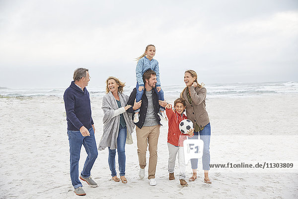 Multi-generation family walking on winter beach