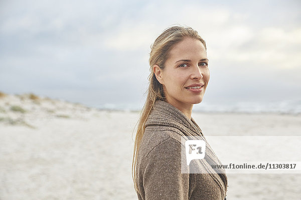 Portrait smiling blonde woman on winter beach