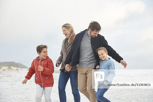 Playful family on winter beach