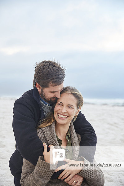 Smiling affectionate couple hugging on winter beach